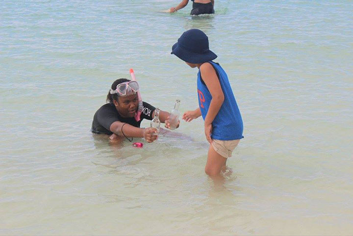 Angelina-Rahming_-EARTHCARE-Eco-Kids-Team-Leader_-hands-----beverage-bottles-found-underwater-to-her-brother_-Aiden-for-proper----disposal--onsh.jpg