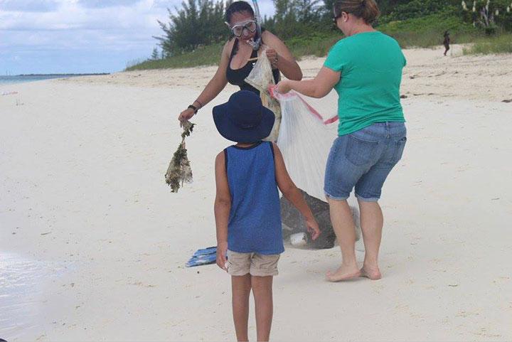 Candice-Woon-hands-marine-debris-to-Linda-----Gembalies-Rahming-as-her-son_-Aiden-Rahming-looks-on.jpg