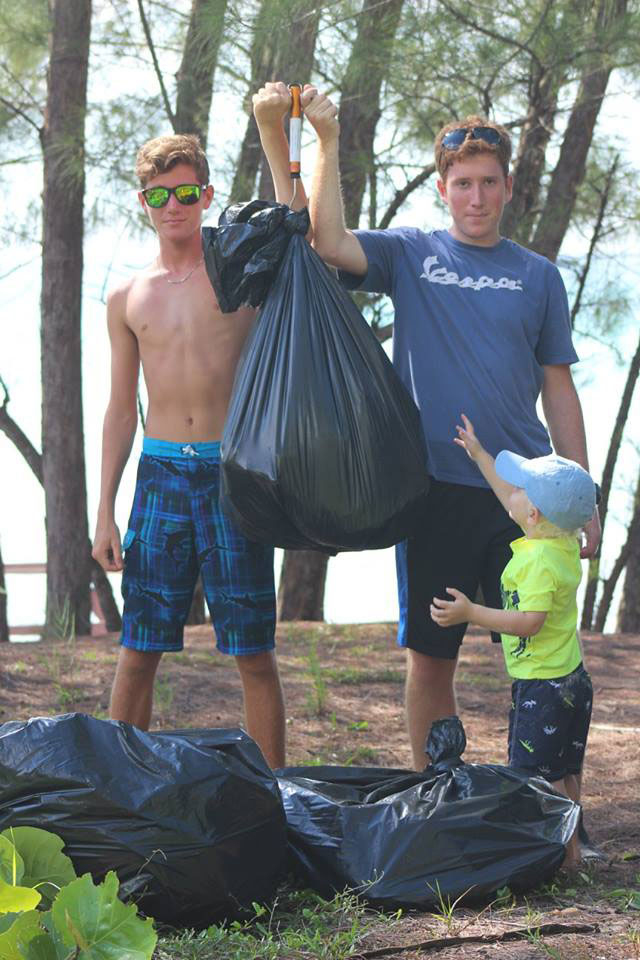 LIS-students_-Austin-Long-and-Stefano-Rulli-wiegh-the------marine-debris--collected-as-Jack-Lowery-looks-on.jpg