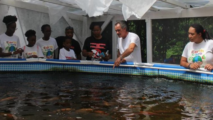 Wayne_Hall_Aquaponics_Manager__________explaining_about_the_tilapia_to_the_EARTHCARE_Eco_Kids_1.jpg