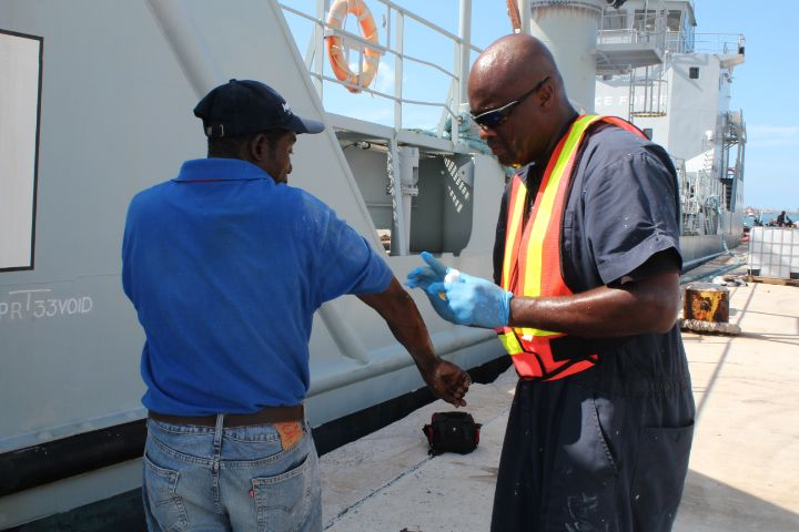 Ph_12_-_Able_Seaman_Alex_Ferguson_rendering_medical_assistance_to_an_Abaco_resident_in_Marsh_Harbour_on_September_7_2019_1.jpg
