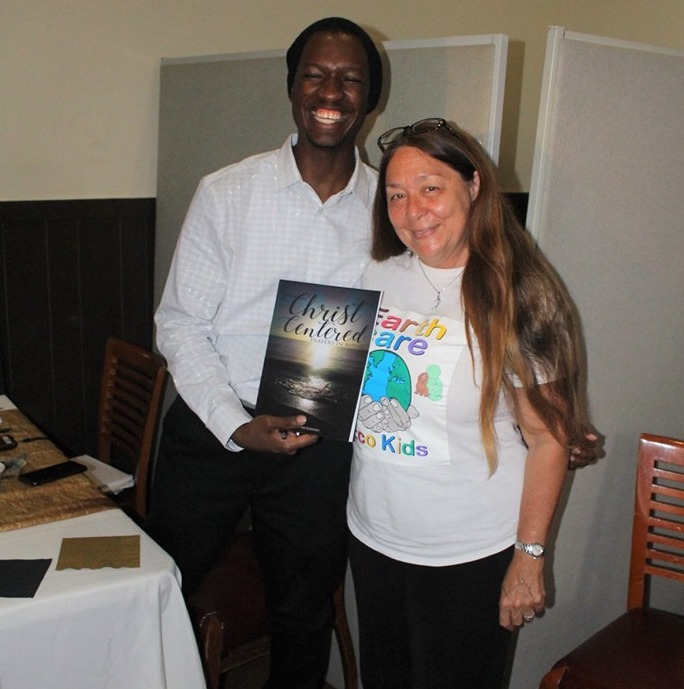 Rudolph_McKinney_presents_his_book_to_Gail_Woon__EARTHCARE_Founder___with_Rudolph_McKinney_Jr.jpg